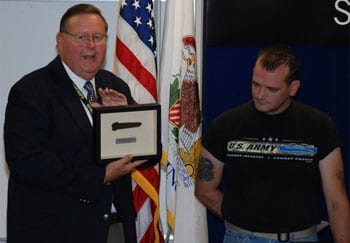 Sheriff Keith Nygren presents the charred knife, framed, to James Halterman. Halterman used the knife, a Gerber Covert 154CM, to cut David Kieffer's seatbelt after his vehicle caught fire. With help from Dan Narcisco, Halterman pulled Kieffer to safety.